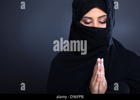 mysterious middle eastern woman praying on black background - Stock Photo