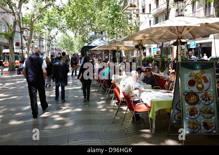 people walking down through street cafes on la rambla barcelona catalonia spain - Stock Photo