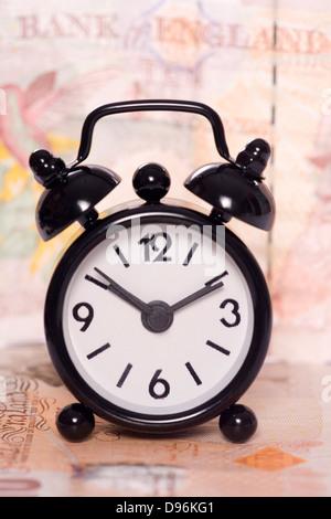 alarm clock on a ten pound note - Stock Photo