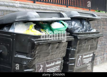Overloaded rubbish bins in St. John's Wood London UK - Stock Photo