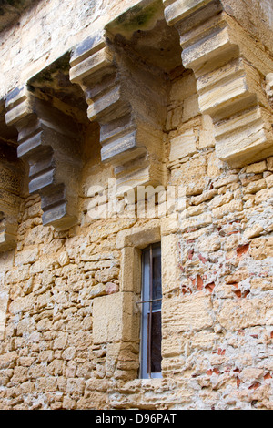 Heavy stone buttresses above narrow window in medieval stone building, Sarlat, France - Stock Photo