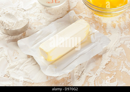 Fresh natural butter in front of baking ingredients - Stock Photo