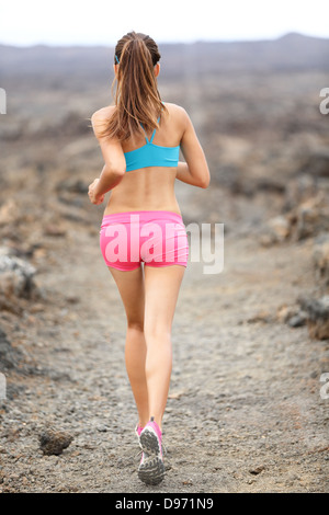 Trail runner woman running cross-country run training outside for marathon. Jogging female athlete working as part - Stock Photo
