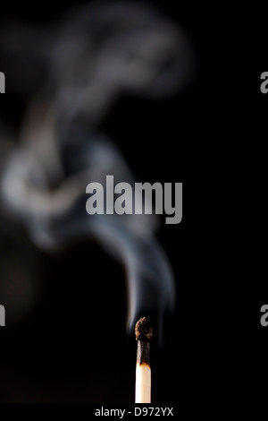 Burnt Wooden Matches smoking against a black background - Stock Photo