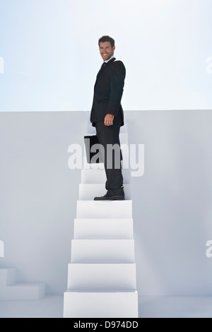 Businessman in black suit with briefcase standing on stairs, smiling, portrait - Stock Photo