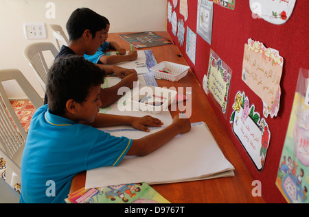 Bedouin children drawing at a day center in Tirabin al-Sana village  built for the Tarabin tribe also known as Al - Stock Photo