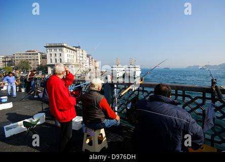ISTANBUL, TURKEY. Fishing in the Golden Horn from the Galata Bridge, with Karakoy ferry terminal and the Bosphorus - Stock Photo