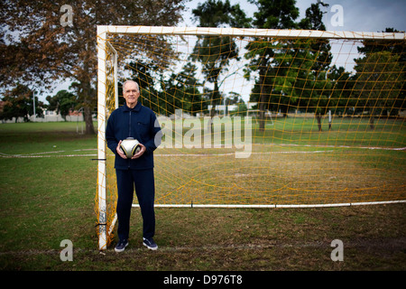 A portrait Albert Uytenbogaadt standing by goal posts holding soccer ball local football grounds in Durbanville - Stock Photo