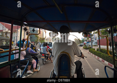 Horizontal view of a local Lao man driving a rickshaw or tuk-tuk down a busy main road in Vientiane. - Stock Photo