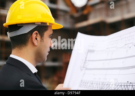 Young man working as engineer in new apartment buildings, looking at building plan in construction site - Stock Photo