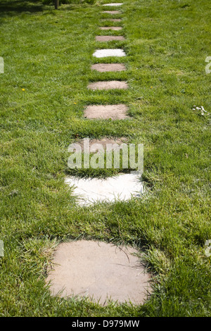 Stepping stone paving slabs form a path across grass lawn in a garden, UK - Stock Photo