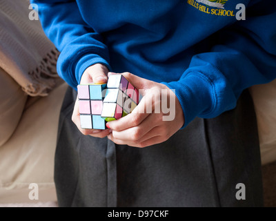 Young girl trying to solve the Rubik`s cube, - Stock Photo