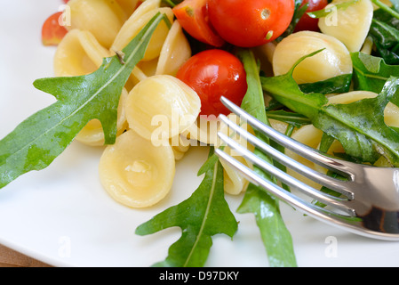 orecchiette pasta with rocket and little tomatoes to be served cold - Stock Photo