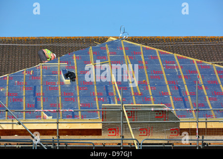 Scaffolding on building construction site & workman fixing foil backed energy saving foam insulation sloping roof on school extension Essex England UK