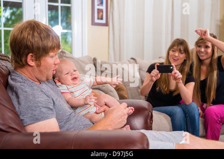 Father holding baby boy while mother with her sister are trying to take a picture on a smart phone camera in the - Stock Photo