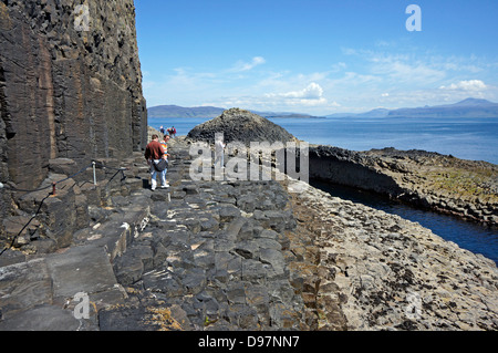 Visitors returning to the pier from fingal's Cave on the path  on Isle of Staffa Inner Hebrides Scotland - Stock Photo