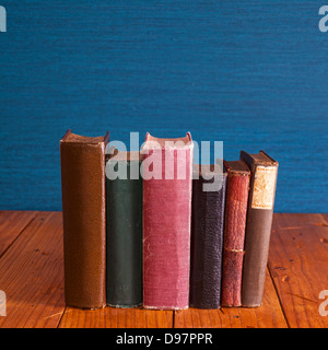 Old Books 0n Rustic Pine Table - old books standing on a rustic pine table with copy space above. - Stock Photo