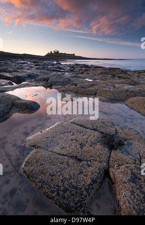 Sunset above Dunstanburgh Castle, Northumberland, England. Spring (May) 2013. - Stock Photo
