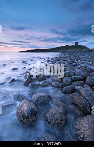 Dunstanburgh Castle at dawn from Embleton Bay, Northumberland, England. Spring (May) 2013. - Stock Photo