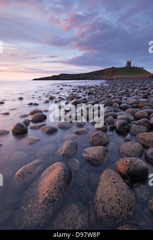 Dunstanburgh Castle from Embleton Bay at dawn, Northumberland, England. Spring (May) 2013. - Stock Photo