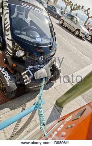 A Renault Twizy electric car gets its battery recharged at an E.on street-side charging station on the Santander - Stock Photo