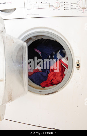 A washing machine, full of clothes, with an open door - Stock Photo