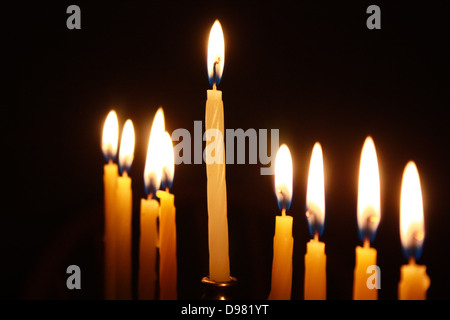 Closeup on candles of lit menorah against black background - Stock Photo