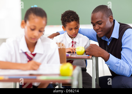 elementary school teacher helping student in classroom - Stock Photo