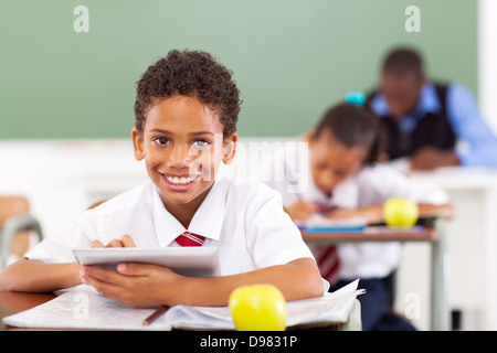 primary school boy using tablet computer in classroom - Stock Photo