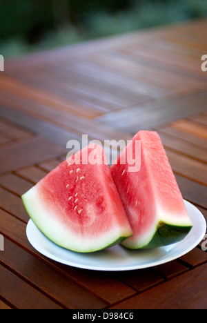 Two slices of fresh pink watermelon on a white plate on a wood outdoor table. - Stock Photo