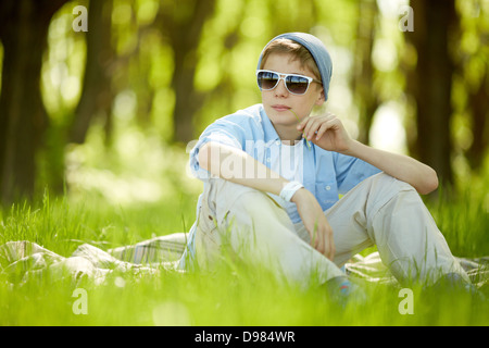 Portrait of cute lad in casual clothes and sunglasses having rest outside - Stock Photo