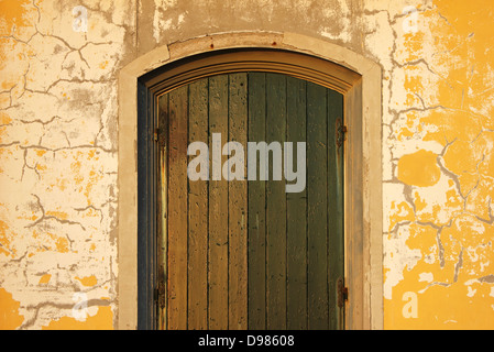 Straight shot of an old entrance door with rusty hinges and cracks on the wall. - Stock Photo