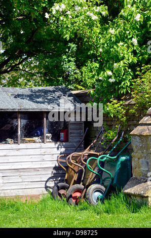Wheelbarrows leaning against a wall by a garden shed. - Stock Photo