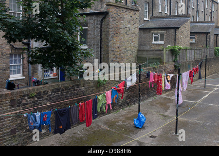 Clothing hanging on a washing line in a Pimlico housing estate in London. Reflecting a bygone era when the residents - Stock Photo