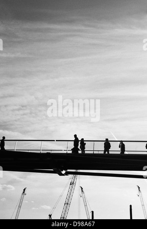 Tourists and workers crossing the Millennium bridge in London in this silhouetted scene, cranes are also seen in - Stock Photo