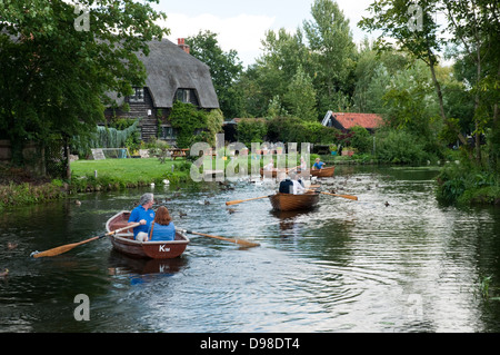 Adults and children seen boating on the river Stour beside a cottage at Dedham. - Stock Photo
