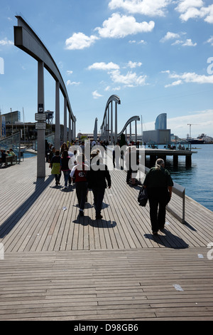 people walking along rambla de mar walkway in the old port of barcelona catalonia spain - Stock Photo