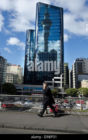 Businessman talks on his mobile phone with the reflection of the Sky Tower in background in Auckland city, New Zealand - Stock Photo