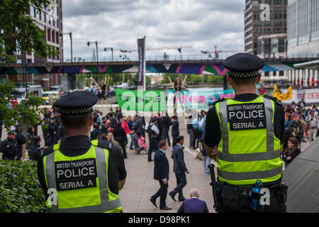 London, UK. 14th June 2013. Police look on as Shift The Debt protesters demonstrate at Canary Wharf ahead of the - Stock Photo