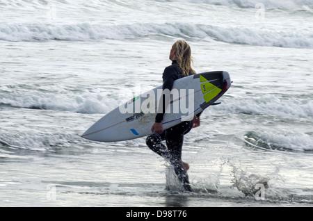 Wave surfer in Piha beach near Auckland, New Zealand - Stock Photo