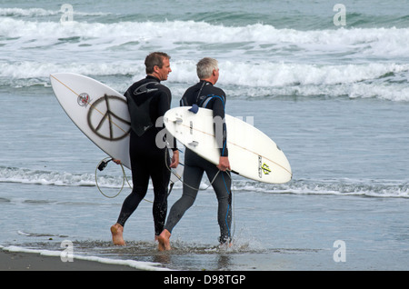 Two mature wave surfers in Piha beach near Auckland, New Zealand - Stock Photo