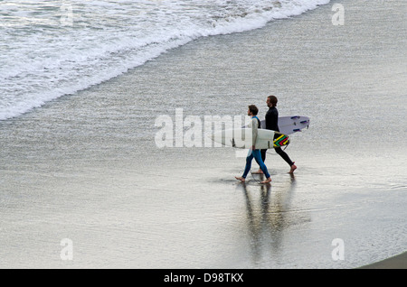 Two young wave surfers in Piha beach near Auckland, New Zealand - Stock Photo