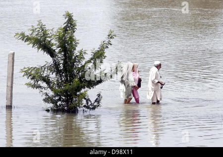 Flood affected people pass through floodwater moving towards safe place after heavy downpour of Monsoon Season at - Stock Photo