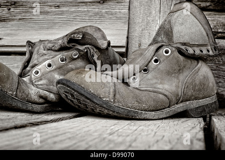 Black & white photo of old weathered hiking boots on wooden porch of Chitina Emporium, remote town of Chitina, Alaska, - Stock Photo