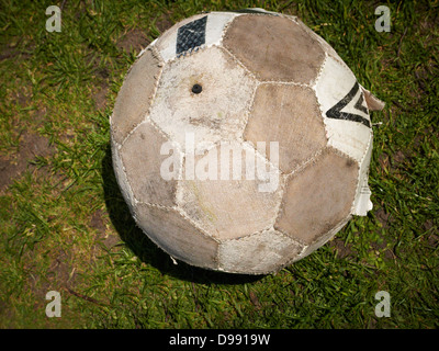 Worn out football on pitch - Stock Photo