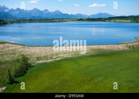 Overlooking the Bannwaldsee in Ostallgaeu, Koenigswinkel Tannheimer Alps, Swabia, Bavaria, Germany - Stock Photo