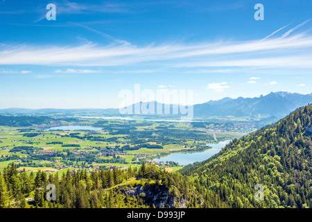 Views of the Allgäu region of Bavaria on villages, mountains, lakes, meadows and forests - Stock Photo