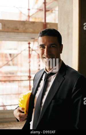 portrait of male engineer smiling and looking at camera in construction site - Stock Photo