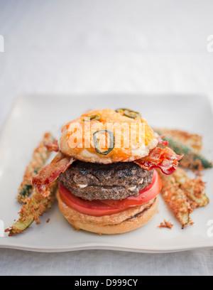 burger bacon tomatoes mustard jalapeno cheese bun and zucchini fries - Stock Photo
