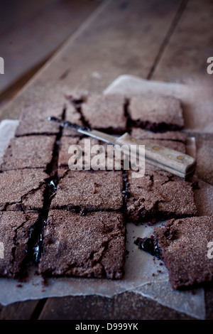 homemade fudge brownies cooling on a wood table - Stock Photo